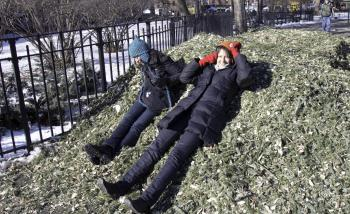Two East Villagers happily rest on top of a pile of Christmas tree mulch at Tomkins Square Park on Sunday (Phoebe Zheng/The Epoch Times)