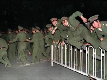 LETHAL FORCE: People's Liberation Army (PLA) soldiers leap over a barrier on Tiananmen Square in Central Beijing June 4, 1989, during heavy clashes with people and dissident students. Chinese troops forcibly marched on the square to end a weeks-long occupation by student protesters, using lethal force to remove opposition encountered along the way. Hundreds of demonstrators were killed in the crackdown as tanks rolled into the environs of the square. (Catherine Henriette/AFP/Getty Images)