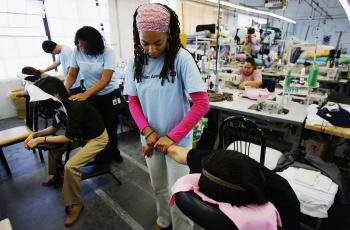 Workers at American Apparel in Los Angeles take a massage break. Unlike many clothing manufacturers in the U.S., American Apparel does not resort to cheap labour or offshoring. Employees work normal hours, are paid more when they are more productive, and  (David McNew/Getty Images)