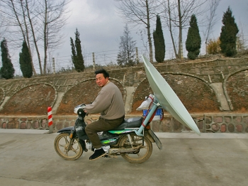A Chinese man carries a TV satellite dish by motorcycle in 2005 in Jinzhai county, Anhui Province of China. (Cancan Chu/Getty Images)