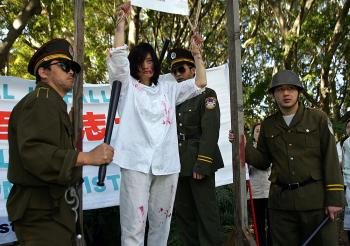 Falun Gong practitioners act out the persecution they receive in China Refugee advocates say Australian Immigration officials often don't understand the fear many asylum seekers have. (Torsten Blackwood/AFP/Getty Images)