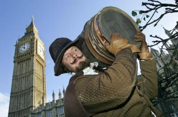 An actor (Bill Hurst) dressed as Guy Fawkes carries a fake barrel of gunpowder into the Houses of Parliament in London.  (Odd Anderesen/AFP/Getty Images)