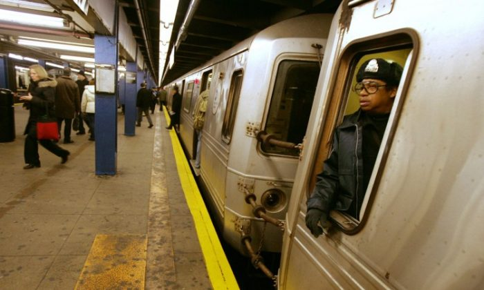 A subway conductor waits for passengers to board the train. (Daniel Barry/Getty Images)