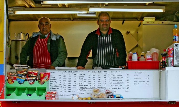 Father and son Ismayil (L) and Ersan Ibrahim work in their portable burger trailer in London, England on April 20, 2006. (Scott Barbour/Getty Images)