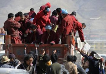 Tibetan Buddhist monks distribute relief goods from a truck amid the earthquake devastation in Jiegu, Yushu county, in China's northwestern Qinghai Province on April 19. (Getty Images)