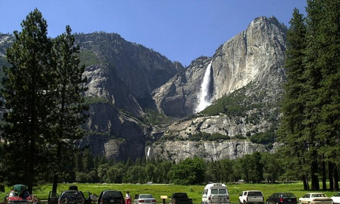 Cars fill a parking lot near Yosemite Falls (background) in Yosemite National Park, Calif. Members of the military will now be eligible for a pass providing free access to national parks and recreational sites across the United States. (David McNew/Newsmakers)