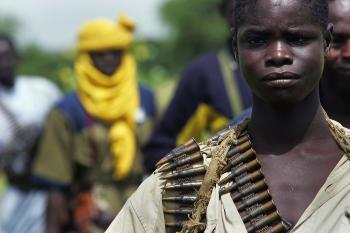 A rebel Sudanese Justice and Equality Movement (JEM) fighter stands at his base near the Chad border in the Darfur region of Sudan on Sept. 7, 2004, in Misterei, Sudan. Violence between Jem and the Sudanese forces escalated this past weekend. (Scott Nelson/Getty Images)