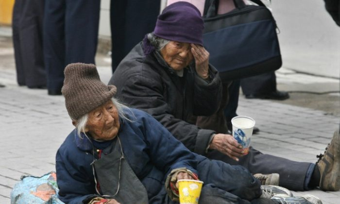 A pair of elderly Chinese women beg on a busy road in Shanghai, in December 2006. The number of elderly Chinese who have been abandoned as their children seek work in the cities is increasing. (Mark Ralston/AFP/Getty Images)
