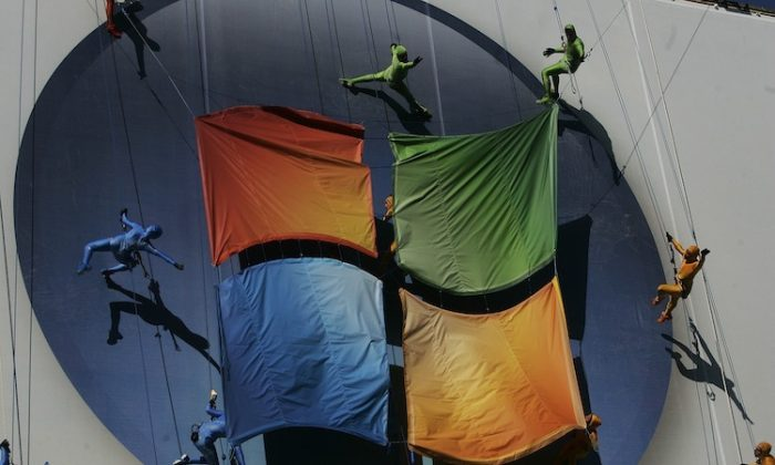 """Members of the """"Grounded Aerial Dance Theater"""" hang from ropes and dance on a poster promoting Vista, a new version of Microsoft Windows, on the side of a warehouse building on Manhattan's west side January 29, 2007 in New York. (Chris Hondros/Getty Images)"""