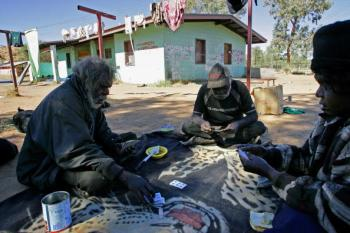 Aboriginal elders George Robertson (L), Toby Gara (C) and Brenda Maxwell (R) playing cards near their house in Hopy's town camp at Alice Springs.  (Anoek De Groot/AFP/Getty Images)