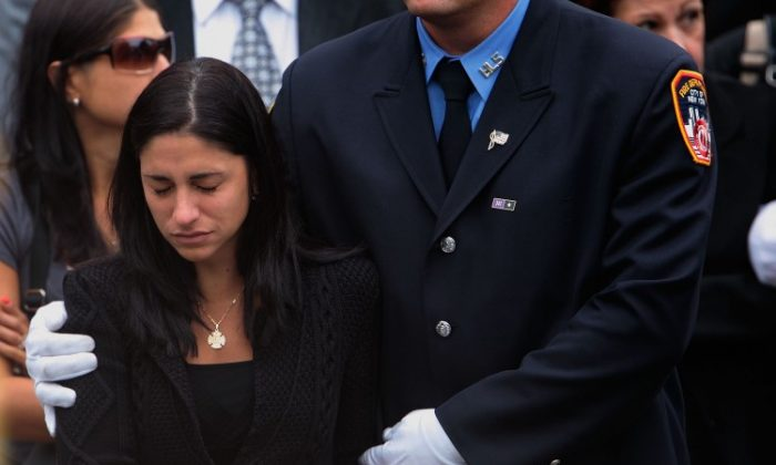 Linda Graffagnino is escorted by a New York firefighter after the funeral of her husband, Joseph Graffagnino, on August 23, 2007 in the Brooklyn borough of New York City. Joseph Graffagnino, 33, was killed along with another firefighter battling a blaze at the abandoned Deutsche Bank building next to Ground Zero on August 18. (Chris Hondros/Getty Images)