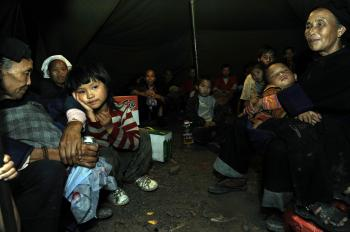 Villagers from a neighboring village where mudslide hits stay in a tent after evacuating from their homes. (The Epoch Times Archive   )