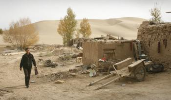 A local walks along the edge of the desert engulfing China's northwest Gansu Province. (Peter Parks/AFP/Getty Images)