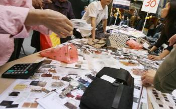 People look at photographs of counterfeit designer bags and watches at a market in the Mong Kok district of Hong Kong 28 November 2007. (Mike Clarke/AFP/Getty Images)