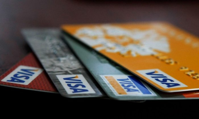 In a file photo, Visa credit cards are arranged on a desk in San Francisco. Visa and MasterCard have agreed to pay more than $7.2 billion in a class-action lawsuit alleging the companies fixed credit card swipe fees. (Justin Sullivan/Getty Images)