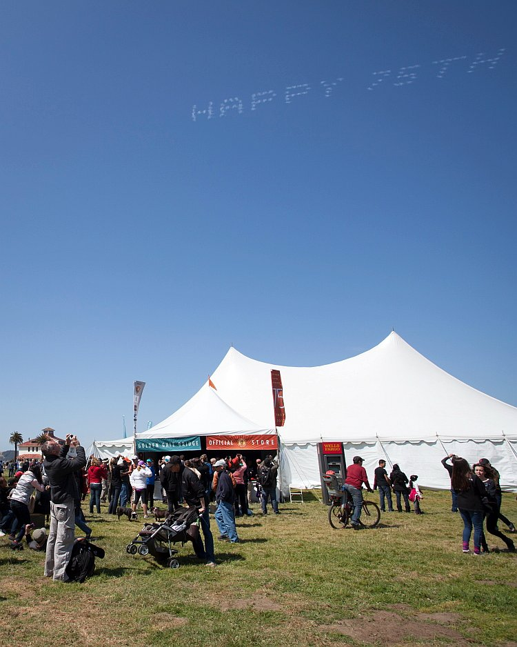 """golden gate bridge People stop to see and photograph """"Happy 75th"""" written in stars in the sky."""