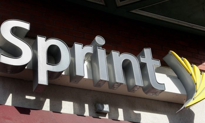 The Sprint Nextel logo hangs above a Sprint retail store Feb. 28, 2008, in Chicago, Ill., in this file photo. Sprint, the nation's third biggest wireless carrier, reported a net loss of $1.3 billion due in part to investing heavily in the iPhone, and spending more than $7 billion in network upgrades. (Scott Olson/Getty Images)