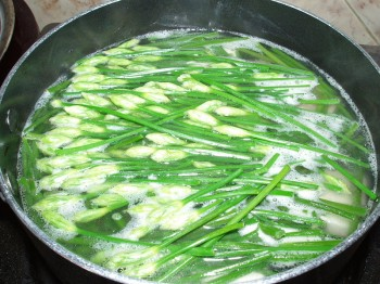 A saucepan containing cooking garlic chive flowers and soft tofu. (Photo by Le Hoan Nha)