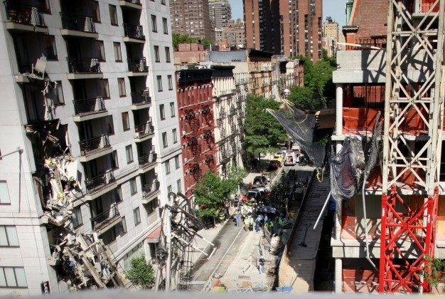 Construction workers walk near the scene of a crane collapse on Manhattan's Upper East Side at 91st Street and 1st Avenue May 30, 2008 in New York. The crane collapsed on top of an apartment building crashing into a penthouse apartment and falling to the ground. (Photo by Yana Paskova/Getty Images)