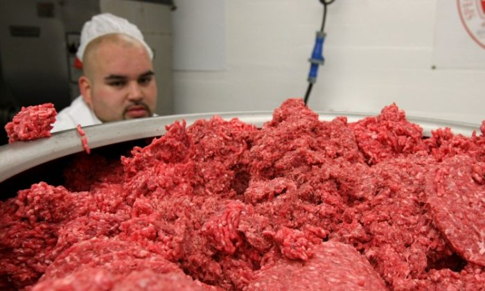 A pile of ground beef passes through a machine that makes hamburger patties at a meat packing and distribution facility June 24, 2008 in San Francisco, California. (Justin Sullivan/Getty Images)