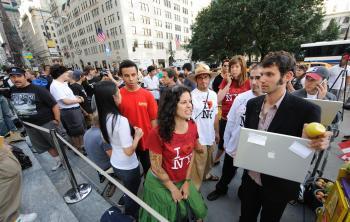 Customers wait outside the Apple store on Fifth Avenue in New York last Friday. About 1,000 tech fans — and at least one confessed `gadget freak` — jostled for a chance to snap up the first iPhone 3Gs.  (DON EMMERT/AFP/Getty Images )