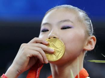 China's He Kexin kisses her gold medal after winning the women's uneven bars final on August 18, 2008. China's Yang Yilin won bronze. Both Chinese gymnasts are at the center of controversy for being underage for Olympic competition. (KAZUHIRO NOGI/AFP/Getty Images)
