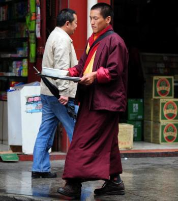 A Tibetan Buddhist monk walks past a Han Chinese man in the town of Kangding in the Tibetan autonomous Garze Prefecture. (Frederic J. Brown/AFP/Getty Images)