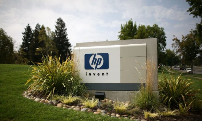 The Hewlett-Packard logo is displayed on the entrance to the HP Headquarters in Palo Alto, Calif. The company is one of the world's biggest makers of PCs and printers, and now those units will become one. (Photo by Justin Sullivan/Getty Images)