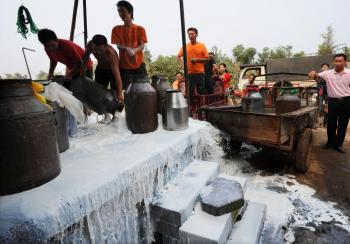 Farmer workers pour away uncollected milk at a farm in Wuhan of Hubei Province, China. (China Photos/Getty Images)