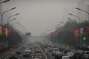 Cars drive through thick smog on a street in Beijing on September 21, 2008. (Peter Parks/AFP/Getty Images)