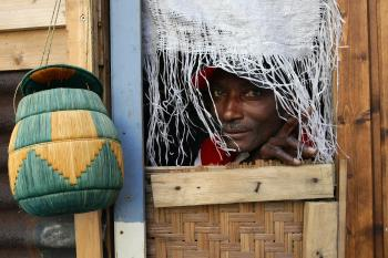 Abioseh Kamara from Medecins Sans Frontieres, peers out from an exhibition refugee camp built in the centre of Sydney last year to raise awareness of asylum seekers. (Torsten Blackwood/AFP/Getty Images)