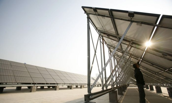 A worker cleans solar panels at a solar photovoltaic power station, under construction in November 2008 in Xining, Qinghai Province, China. (China Photos/Getty Images)