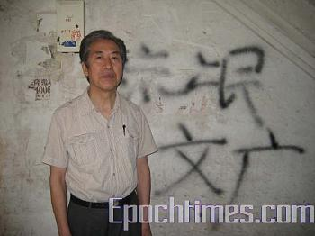 """Professor Sun Wenquang, standing in front of the wall of his apartment building in Shandong University. The wall was painted with insulting words like """"traitor,"""" """"rapist Sun Wenquang,"""" """"rougue Sun Wenguang,"""" and """"rogue Sun,"""" etc. on June 2 (The Epoch Times)"""