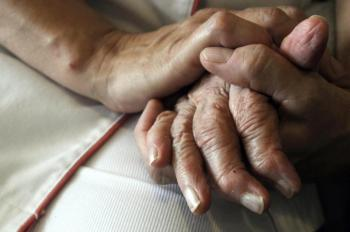 A nurse holds the hands of a person suffering from Alzheimer's disease on September 21, 2009 at Les Fontaines retirement home in eastern France. (Sebastien Bozon/AFP/Getty Images)