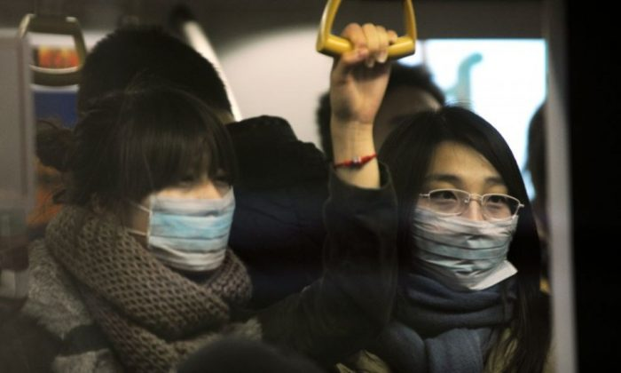 Two women wear masks while riding on the Beijing subway. (Peter Parks/AFP/Getty Images)