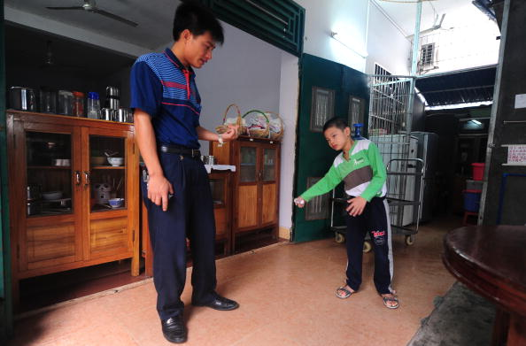 Huang Xiangyi (L) encourages his seven year-old son Huang Zhuoxiang, who suffers from cerebral palsy, to walk on Oct. 26, 2009 in China. (Frederic J. Brown/AFP/Getty Images)