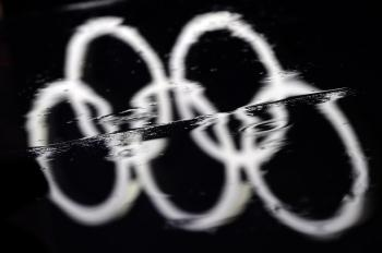 The Olympic rings are reflected in a rain puddle at the Vancouver 2010 Winter Olympics.  (Fabrice Coffrini/AFP/Getty Images)