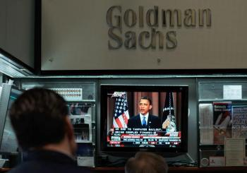 Financial professionals in the Goldman Sachs booth on the floor of the New York Stock Exchange at midday watch President Obama give a speech about Wall Street financial reform on April 22, in New York.  (Chris Hondros/Getty Images)