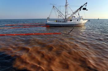 A shrimp boat passes through a heavy oil slick as it uses the deployed oil boom and absorption pads to collect the oil from the massive oil spill on May 5.  (Joe Raedle/Getty Images)