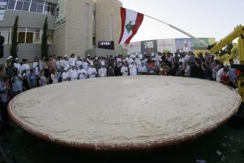 Hummus World Record: Lebanese chefs celebrate around the largest plate of hummus after setting a new Guinness world record in Beirut on May 8. The massive hummus serving weighed in at 10,452 kilograms (23,520 pounds), the size of Lebanon in square kilometers. (Anwar Amro/Getty Images)