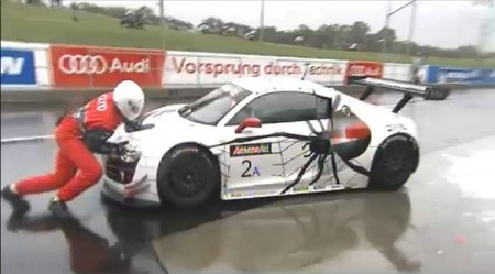 A crewman tries to push the #2 Audi back into its pit stall after it drove off with the fuel hose attached. (bathurst12hour.com.au)