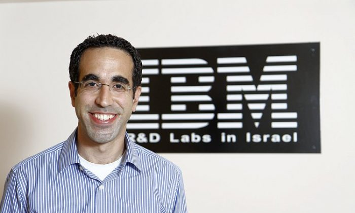 Shaharabani, a senior expert for data security at IBM, stands for a photo near the company logo at his office in Israel. (Epoch Times Staff)