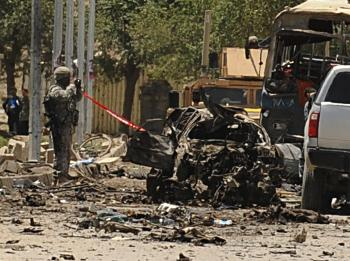 Afghan and foreign investigators inspect the site of a suicide car bomb  in Kabul on May 18. The attack has targeted NATO troops in the Afghan capital, killing at least 20 people. It is the deadliest strike on Kabul in more than a year. (Shah Marai/Getty Images)