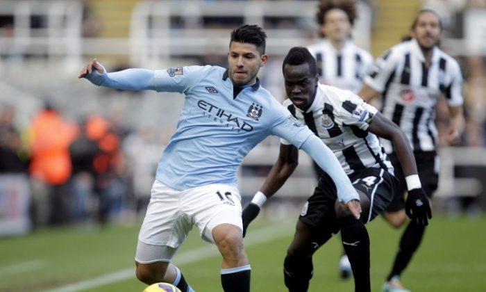 Manchester City's Sergio Aguero fends off Newcastle's Cheik Tiote in English Premier League action on Saturday, Dec. 15, 2012. (Graham Stuart/AFP/Getty Images)
