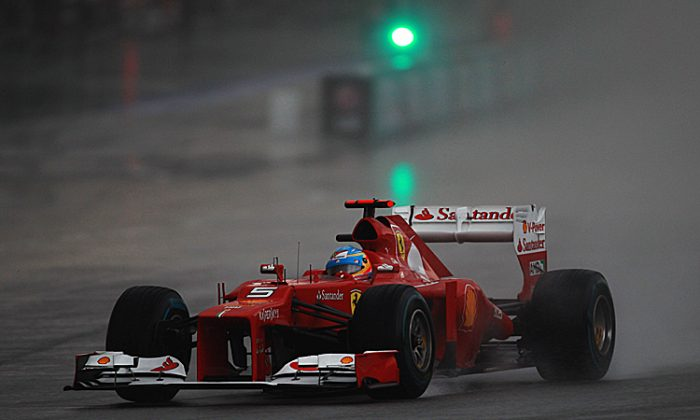 Fernando Alonso of Ferrari drives through the rain on his way to winning the Formula One Malaysian Grand Prix. (Mark Thompson/Getty Images)