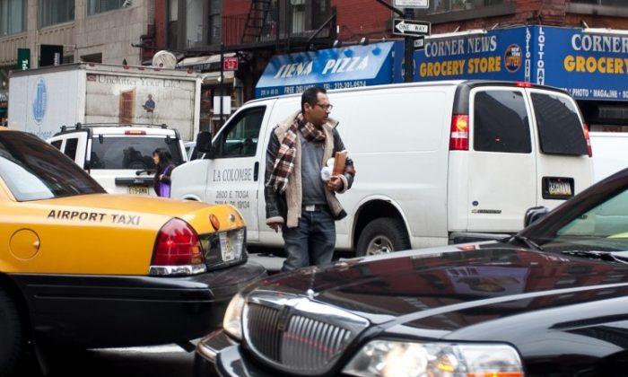 A Pedestrian in Midtown Manhattan walks across the street on Feb. 15. (Amal Chen/The Epoch Times)