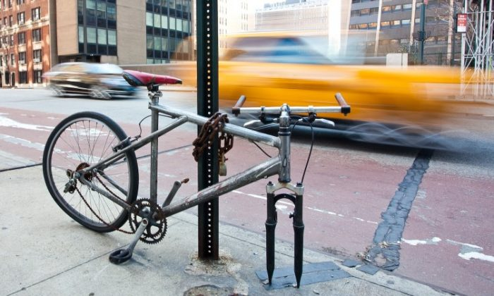 A rusty bike with a bent back tire and missing front tire on 34th Street near 11th Avenue. (Amal Chen/The Epoch Times)