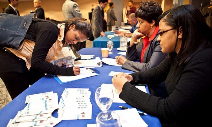 A woman fills out an employment form at a job fair in Midtown Manhattan on April 18. (Amal Chen/The Epoch Times)