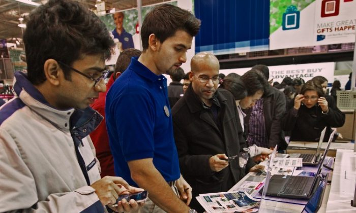 Black Friday customers are assisted by a Best Buy worker in the computer department at the Fair Lakes Best Buy store in Fairfax, Va., in this file photo. Social media, search engines, and mobile apps are transforming the Black Friday shopping extravaganza; however, dangers and benefits alike come with the new tools. (Paul J. Richards/AFP/Getty Images)