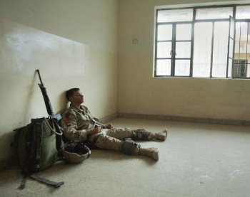 An exhausted U.S. Army soldier takes a short break after engaging enemy forces all night during heavy fighting in Fallujah, Iraq, in this file photo.  (Scott Nelson/Getty Images)